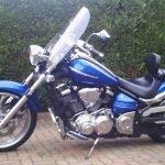 Blue, 1900cc Yamaha Raider, 2008, with screen, panniers and sissy bar.