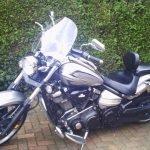 Silver, 1900cc Yamaha Raider, 2010, with screen, saddle bags and sissy bar.